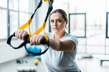 confident overweight woman training arms with suspension straps in gym