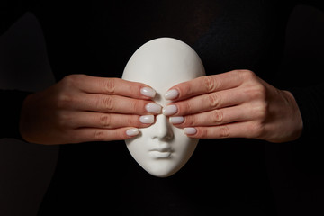 Woman's fingers close eyes of gypsum mask face on a black background. See no evil. Concept three wise monkeys.