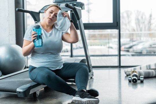 tired plus size woman wiping sweat with towel while sitting on treadmill and holding bottle with water