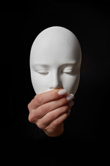 Plaster face mask with closed mouth on a black background. Speak no evil. Concept three wise monkeys