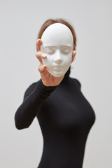 Young woman in a black sweater with plaster mask in her hand instead of face on a white background. Concept The masks we wear
