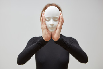 Attractive girl in a black jumper holds gypsum mask sculpture instead of face on a white background. Concept The masks we wear