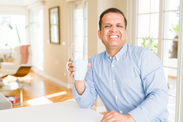 Middle age man enjoying and drinking a cup of coffee at home