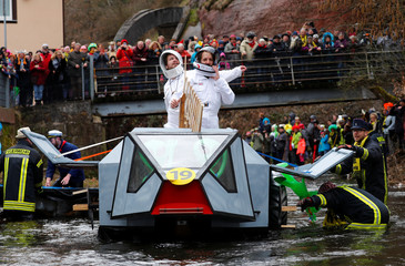 Carnival revellers ride down the Schiltach stream during the 'Bach na fahre' raft contest in Schramberg