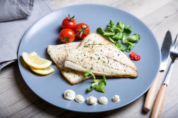 Fried fillet dorado (fish) with tomatoes, lemon and corn salad. Selective focus, close-up.