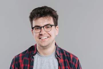 man, looking into the camera, in glasses, close-up, checkered shirt,  gray background, isolated, positive facial emotion,  copy space
