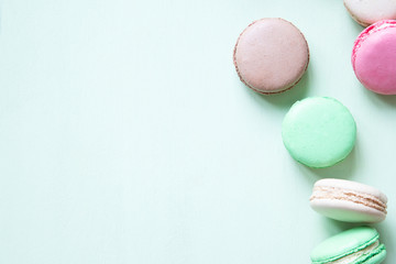 Fotobehang Colorful macaron or macaroon cakes on pastel green background with copy space.
