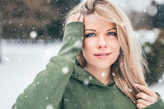 Beautiful young woman with a dreamy facial expression straightens her hair - an external portrait in the winter in the snowfall - is dressed in hoodie