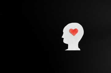 The image of a man and a heart on his head on a black background from a cardboard template. Heart in thoughts of love