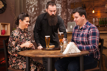 Hipster barman giving the order to beautiful young couple.