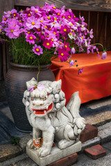 Small lion-dog stone statue in front of a large vase with flowers. Lion-dogs or Komainu are the guardians of the gates to shrines and houses.