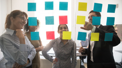 Diverse team people looking at sticky notes on glass brainstorming