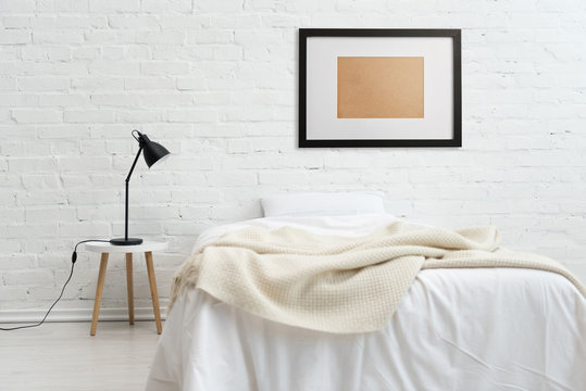 modern bedroom with bed and black frame on white brick wall