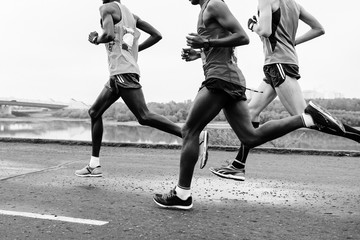 group runners leaders run along embankment of river black-and-white image