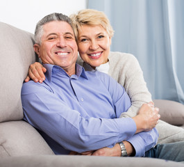sweet mature married couple in house are warmly reconciled after quarrel