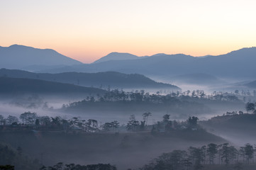 Wall Murals Fog cover small village at the foot mountains with the magical of light at dawn