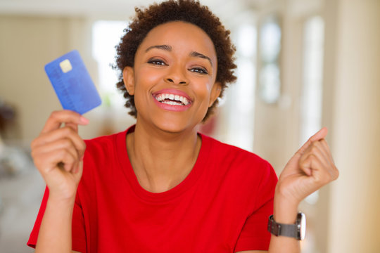 Young african american woman holding credit card screaming proud and celebrating victory and success very excited, cheering emotion