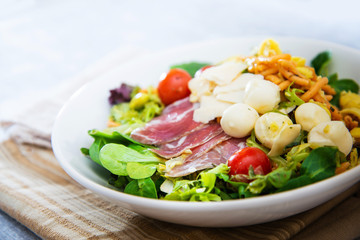 Salad with speck ham and egg, tomatoes