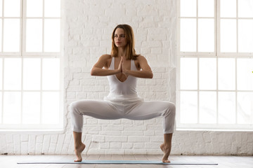 Attractive woman standing in Goddess pose, Sumo Squat, yoga exercise