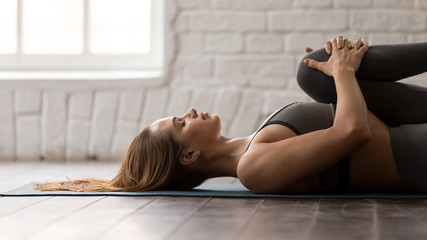 Girl practicing yoga, lying in Knees to Chest pose, Apanasana