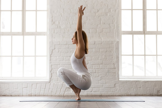 Sporty woman standing in Utkatasana pose, Squat, Chair exercise
