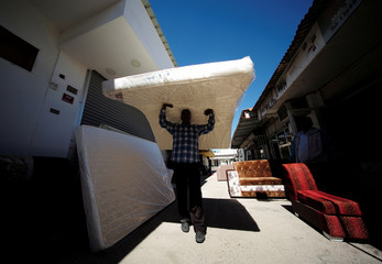 A worker carries a mattress on his head to deliver it to his customers at the flea market in Isa Town south of Manama