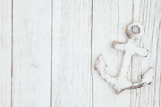 A anchor on weathered whitewash textured wood background