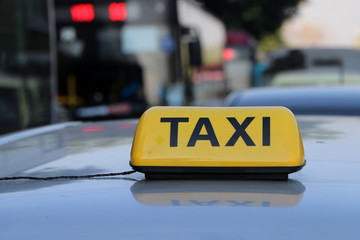 Taxi light sign or cab sign in yellow color with black text on the car roof.