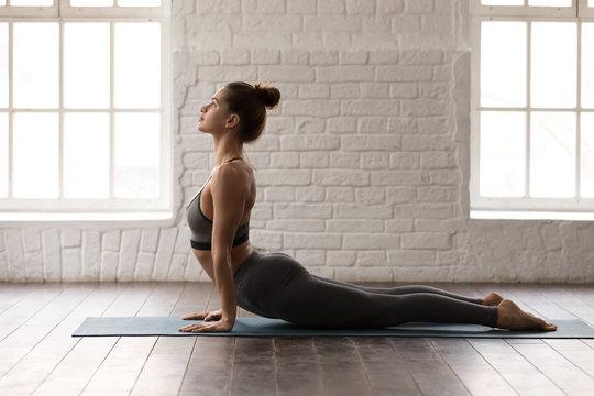Young woman practicing yoga, lying in Cobra pose, Bhujangasana