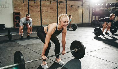 Fit young woman weightlifting during a gym class