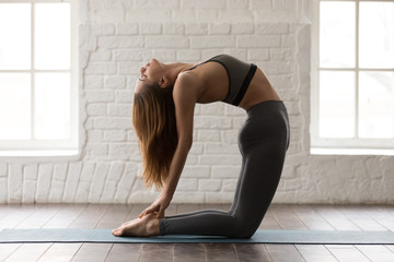 Young woman practicing yoga, standing in Ustrasana pose, Camel exercise