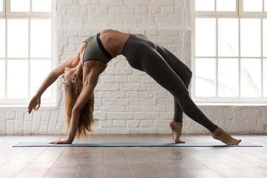 Beautiful woman practicing yoga, standing in Wild Thing pose, Camatkarasana