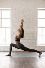 Woman practicing yoga, standing in anjaneyasana pose, Horse rider, vertical