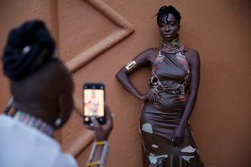 A woman takes a picture of a model behind the scenes of a fashion show featuring African fashion and culture during a gala at the African heritage house in Nairobi