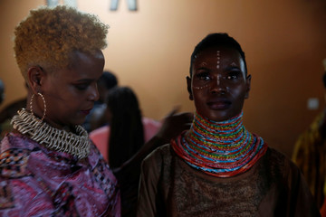 A model receives final touches behind the scenes of a fashion show featuring African fashion and culture during a gala at the African Heritage House in Nairobi