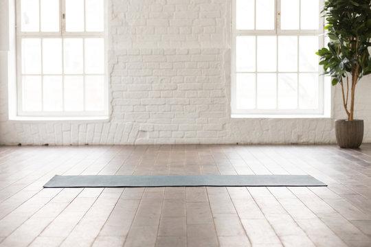 Yoga mat on natural wooden floor in empty room