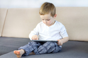 Little boy sitting on the sofa at the living room and using touchscreen tablet. Happy smart child playing game on tablet computer. Education, technology, children's security and fun concept.
