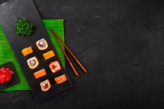 Japanese sushi chopsticks over soy sauce bowl, rice on black stone background. Top view with copy space