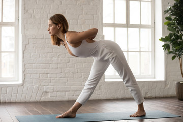 Sporty woman practicing yoga, standing in Parsvottanasana pose