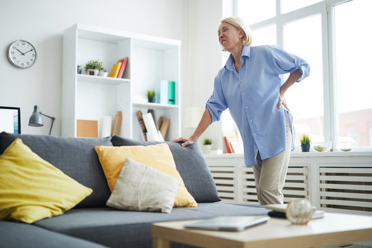 Portrait of modern senior woman suffering from back pain leaning on sofa, copy space