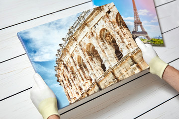 Photography printed on canvas with gallery wrap method of canvas stretching in male hands. Images of architectural landmarks of France