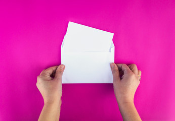 A woman hands holds a envelope and post card on isolated background