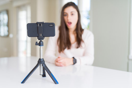 Beautiful young woman recording selfie video with smartphone webcam scared in shock with a surprise face, afraid and excited with fear expression