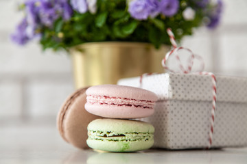 Fotoväggar - Macaron cookies, gift boxes and flowers on white wall background
