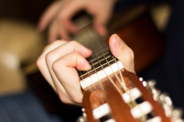 Classical guitar in the hands of a young guy.