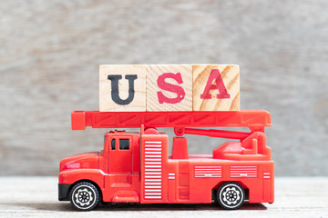 Red fire truck hold letter block in word USA (United states of America) on wood background