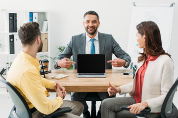 advisor pointing with fingers at laptop with blank screen near man and woman thumbing up in office