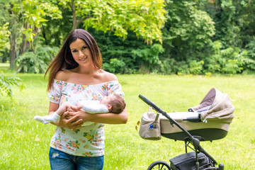 A mother standing next to a stroller and holding her baby
