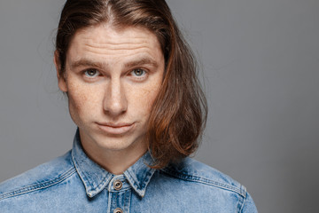 Portrait of a handsome long-haired man with freckles dressed in a denim shirt