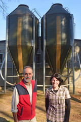 portrait of a couple farmers on the outside of a grange with  grain storege